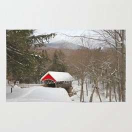 Red covered bridge in snowy landscape Rug