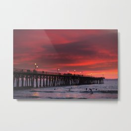 Surfers riding waves off Seal Beach pier at sunset Metal Print