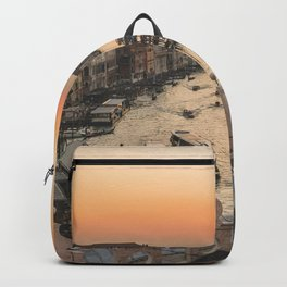 SHIPS ON BODY OF WATER BETWEEN HOUSES AND BUILDINGS DURING GOLDEN HOUR Backpack