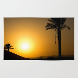 Golden Andalusian sunset with silhouette palm trees and mountain Rug