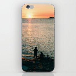 Three fisherman enjoy a beautiful sunset at the shore of 'Colonia del Sacramento, Uruguay'. iPhone Skin