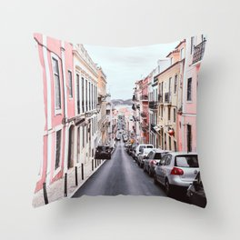 LINE OF VEHICLES ON THE RIGHT SIDE OF A 2-WAY ROAD IN THE MIDDLE OF PINK AND YELLOW BUILDINGS DURING DAY Throw Pillow