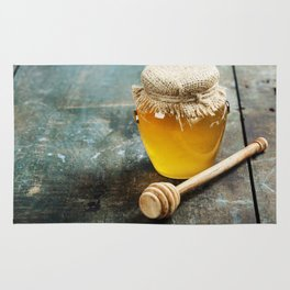 Honey jar and dipper on wooden background Rug