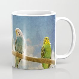 Parakeets perched on a branch againts a cloudy blue sky Coffee Mug