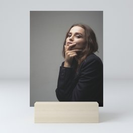 Girl in jacket covers her face with her hand Mini Art Print