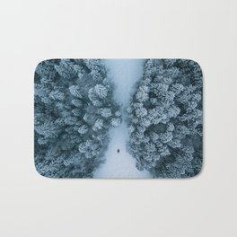 Man lying in the snow on a frozen lake in a winter forest - Landscape Photography Bath Mat