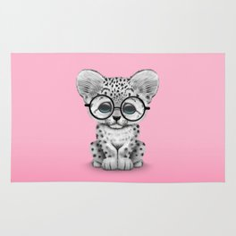 Cute Snow Leopard Cub Wearing Glasses on Pink Rug