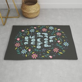 BE PROUD OF WHO YOU ARE - Motivational quotes hand drawn illustration with flowers on dark backgroun Rug