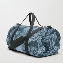 Man lying in the snow on a frozen lake in a winter forest - Landscape Photography Duffle Bag
