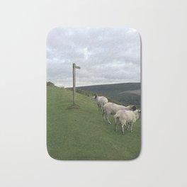 Guidepost amongst sheep Bath Mat