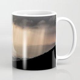 Sunbeams illuminate the hills below Coffee Mug