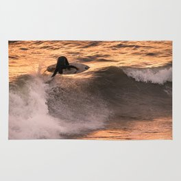 Surfer grabs air on wave at sunset Rug
