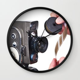 Retro mechanical hobbies movie camera and film in hands Wall Clock