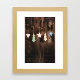 Wooden Christmas ornaments hanging on rustic wall Framed Art Print