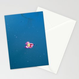 A pink blossom floating in a contrast blue lake Stationery Cards