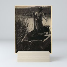 Doris Ulmann  (1882–1934), Black man in hat and overalls, holding net, standing in boat on small wat Mini Art Print