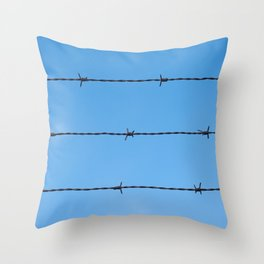 Contseptual shot of barbed wire over blue sky Throw Pillow