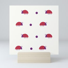 Red ladybugs and purple dots over light yellow background Mini Art Print