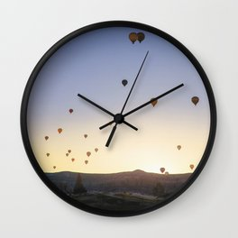 Hot air balloons are seen over rock formations in Nevsehir, Turkey. Wall Clock