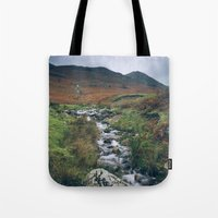 cassia beck Tote Bags featuring Cinnerdale Beck with Whiteless Pike beyond. Lake District, UK. by liamgrantfoto