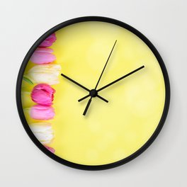 Row of multicolored tulips for border or frame over yellow blurred background Wall Clock