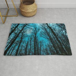 The sky is blue over the forest Rug