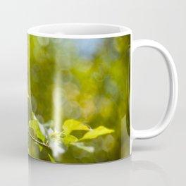 Green leaves and bokeh effect Coffee Mug