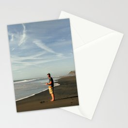 boy on black sand beach in new zealand Stationery Cards