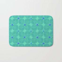 Blue starfish on green sand Bath Mat