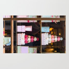 Beautiful colorful tasty macaroons cakes sweets and presents in the boxes display in window at the  Rug