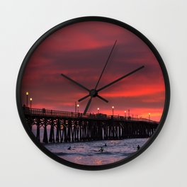 Surfers riding waves off Seal Beach pier at sunset Wall Clock