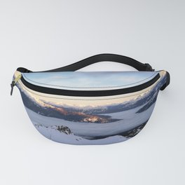 Morning light sweeping mountain peaks above sea of clouds Fanny Pack