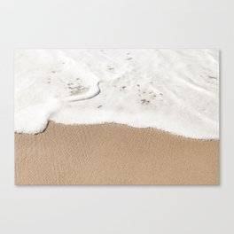 Wave gently washes up on a sandy beach Canvas Print