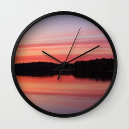 Serene view of calm lake and tree silhouettes at twilight Wall Clock