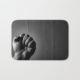 powerful clenched fist, black and white Bath Mat