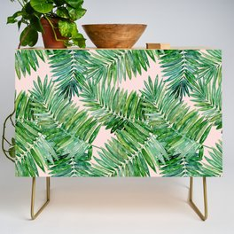 Green palm leaves on a light pink background. Credenza
