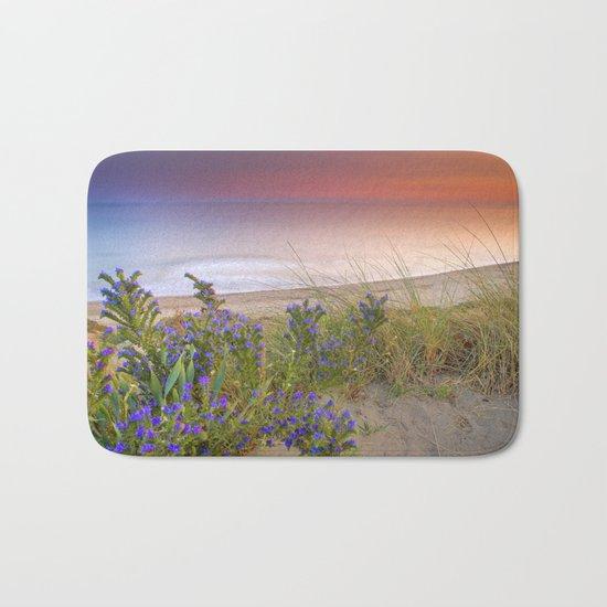 """Purple flowers at the sea sunset"" Bath Mat"