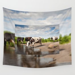 Herd of cows walking across puddle Wall Tapestry
