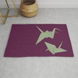 Origami paper cranes on purple waves Rug