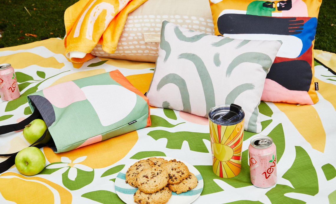 outdoor blanket with pillows, blankets, bags and a plate of cookies