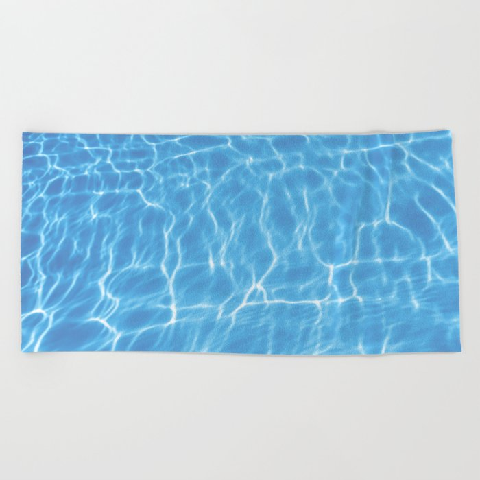 Blue ripped water in swimming pool background Beach Towel by allexxandarx