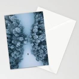 Man lying in the snow on a frozen lake in a winter forest - Landscape Photography Stationery Cards