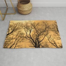 Orange sky, naked trees, haunting forest Rug