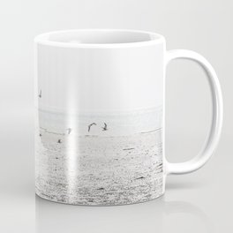 Seagulls fly over a beach in Normandy Coffee Mug