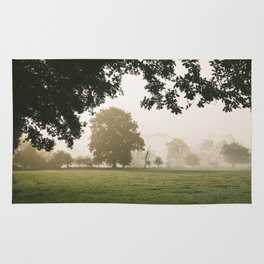 Sunrise burning through heavy fog over countryside scene. Norfolk, UK. Rug