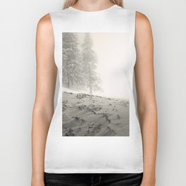 Snow covered mountain hill with snow covered pine forest in blizzard Biker Tank