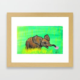 Baby elephant in the green fields smelling a pink rose by Jana Sigüenza Framed Art Print