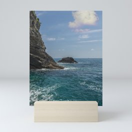rocky cliff by the sea and a huge cottony cloud in the sky above a small imperceptible boat Mini Art Print