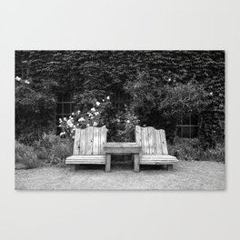 Wooden chairs and table in overgrown garden Canvas Print
