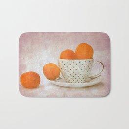 a cup full of apricots Bath Mat